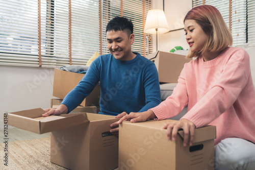 Obraz na plátně  Young happy Asian couple moving to their new home, open boxes to check old objects from old home