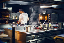 Cook Stands With His Back, Cooking In A Modern Kitchen, In A Restaurant. Low Key. Copy Space For Text