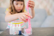 Leinwanddruck Bild - Adorable little girl making slime closeup photo