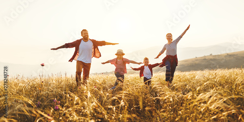 Fotografiet  Happy family: mother, father, children son and daughter on sunset