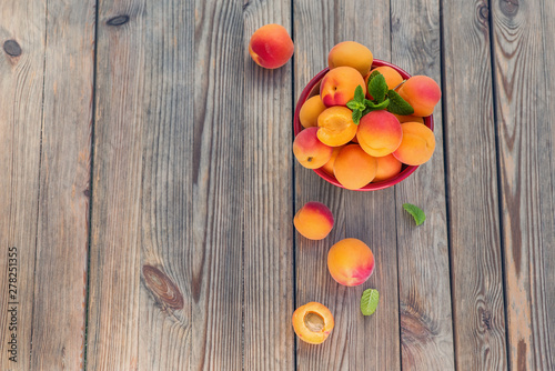 obraz PCV Ripe apricots in a bowl on wooden rustic background copy space
