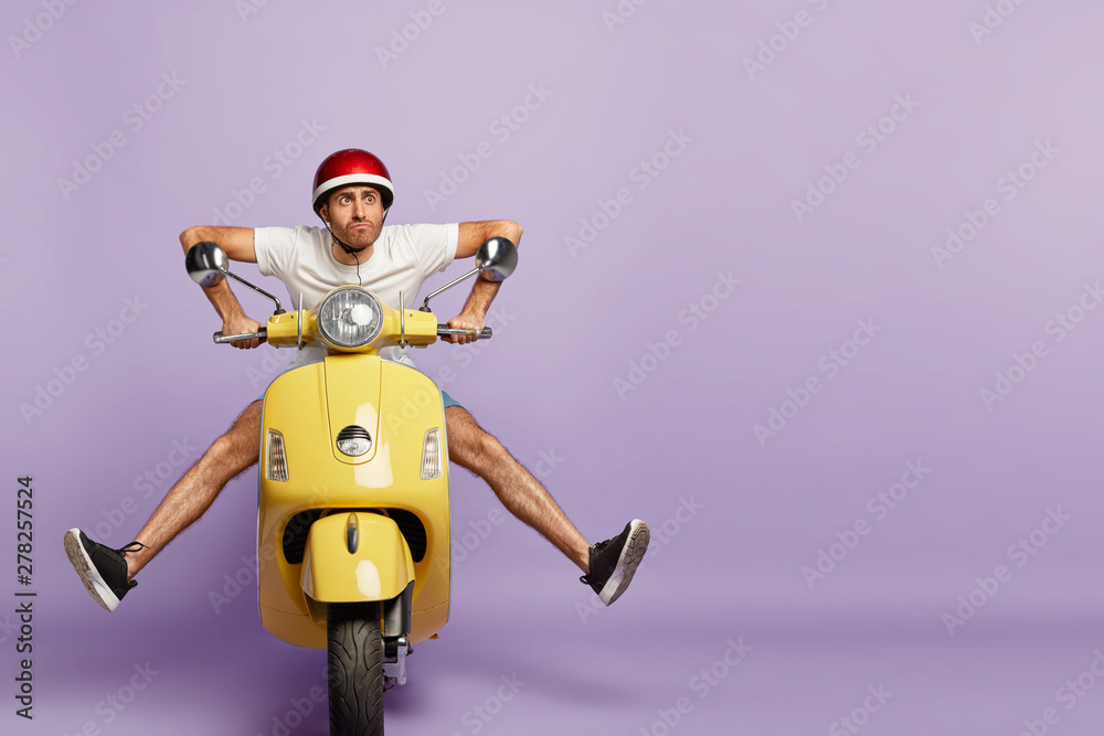 Fototapety, obrazy: Funny young man with fasten motorbike helmet, poses on fast bike, wears white t shirt and sneakers, poses against purple background with empty space. People, transportation and riding concept