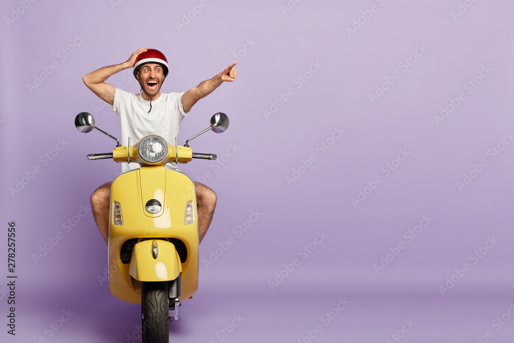 Fototapety, obrazy: Surprised active man rides fast motorbike, points into distance, stares with shock, notices something incredible, wears protective helmet, isolated on purple background with blank copy space