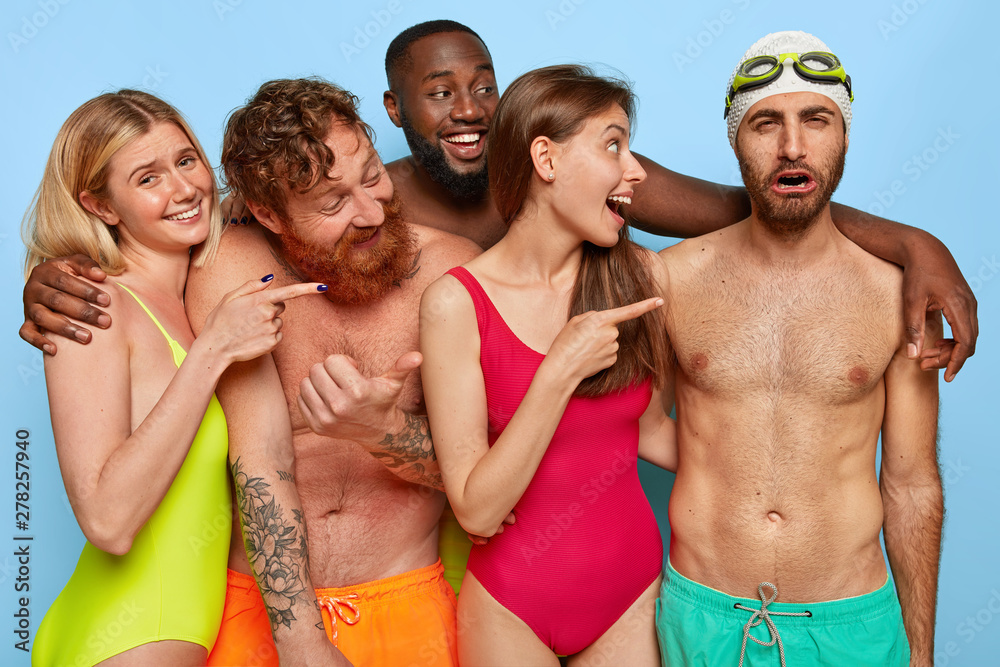 Fototapety, obrazy: Crowd of cheerful diverse friends point at funny dejected guy in trunks, swimcap and goggles, laugh he cannot swim, enjoy holiday all together in resort place. Summer party and friendship concept