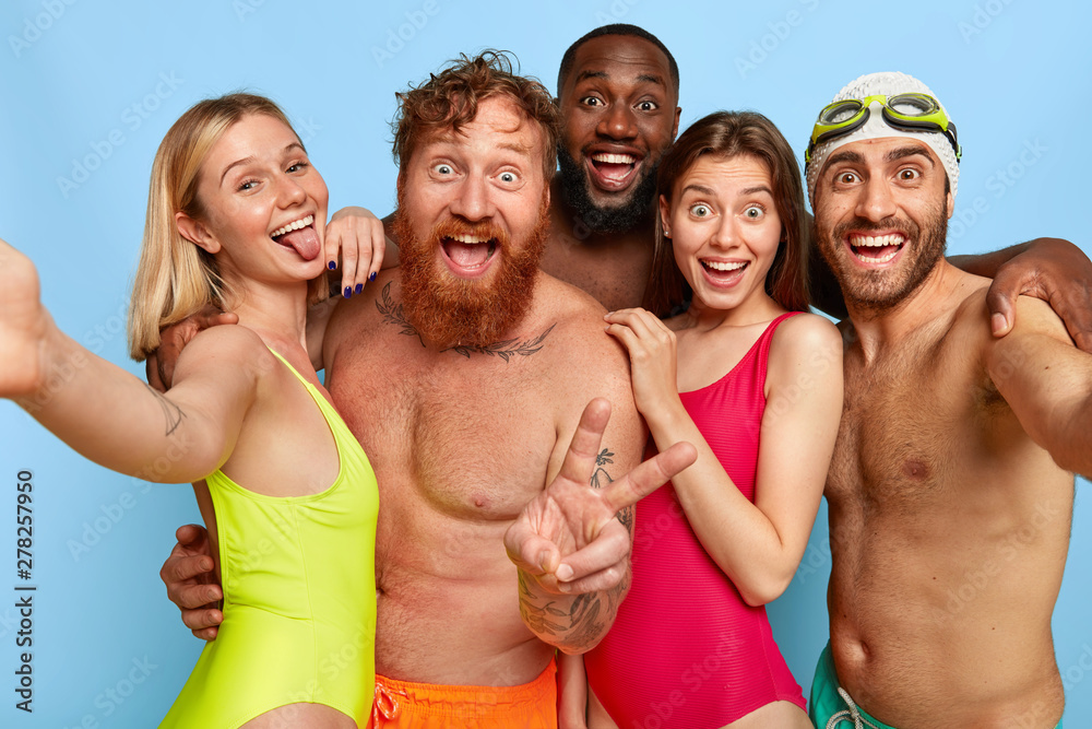 Fototapety, obrazy: Multiracial group of young friends make selfie photo, show tongue and peace gesture, spend weekend at beach during summer, have funny outdoor activities. Friendship, leisure, vacation concept