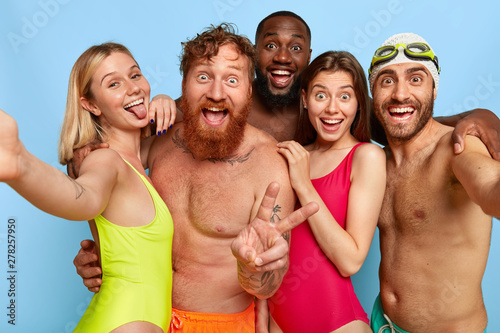 Poster Ecole de Danse Multiracial group of young friends make selfie photo, show tongue and peace gesture, spend weekend at beach during summer, have funny outdoor activities. Friendship, leisure, vacation concept