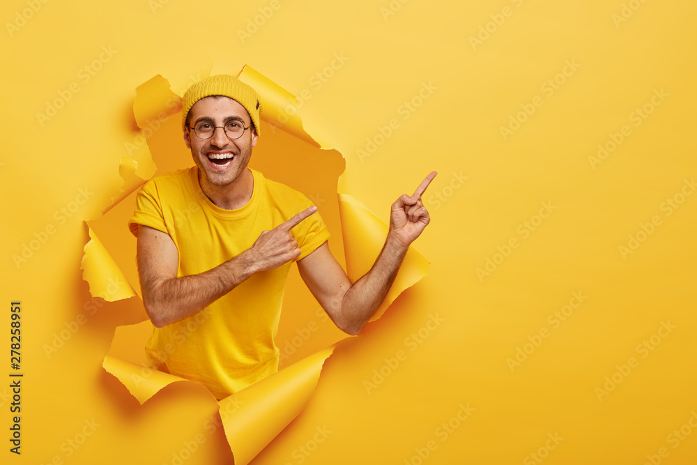 Fototapety, obrazy: Handsome positive guy points away on right side, shows free space for your promotional information, stands in paper hole, wears yellow casual outfit and hat. People, advertisement, good mood concept