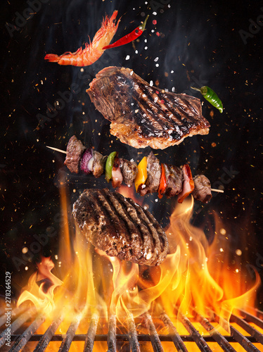 Fotomural  Tasty beef steaks and skewers flying above cast iron grate with fire flames