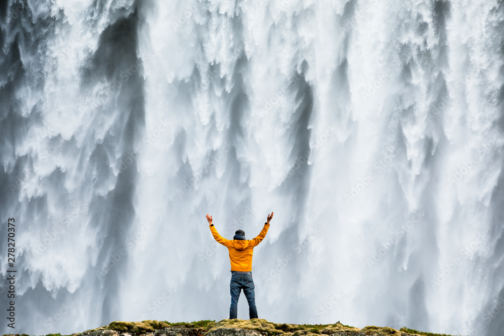 Fototapety, obrazy: Man admirnig the beauty of iconic Skogafoss waterfall in Iceland, Europe.