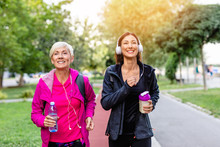 Happy Mother And Daughter Jogging Together Outdoors In Park.