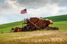 Fourth Of July Patriotism On An Old Harvester. An American Flag Flies Over An Abandoned Wheat Harvester In The Palouse Area Of Eastern Washington State.