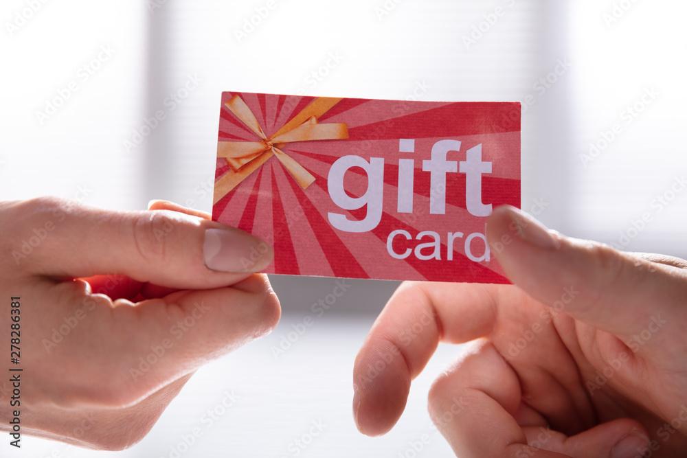 Fototapeta Female Hand Giving Gift Card To Her Partner