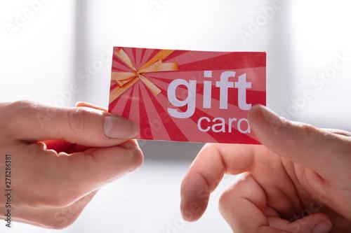 Fotografia Female Hand Giving Gift Card To Her Partner