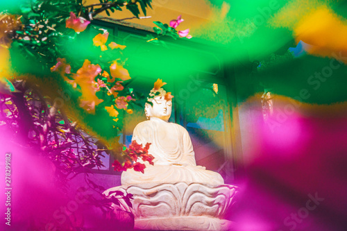 Tuinposter Historisch mon. Stone carved statue of Buddha surrounded with colorful flowers