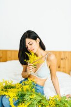 Brunette Girl With Mimosa Plants In Her Hands
