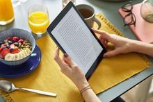 Woman Reading Ebook Via Tablet...