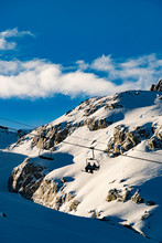 Silhouette Of 2 Skiers Riding A Chairlift On A Sunny Day