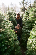 Young Mother Walking With Son Outside At Christmas Tree Farm Dur