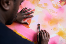 Back View Of Painter Hands Painting Abstract Canvas Artwork.