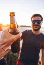POV Shot Of A Man Toasting A Bottle Of Beer With A Friend On The Beach At Sunset