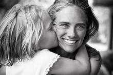 Little Blonde Girl Kisses Mother