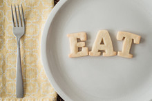 """Shortbread Cookie Letters Spelling Out The Word """"""""eat"""""""" In A Place Setting"""