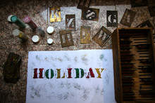 The Word Holiday Spelled Out With Glitter Using Stencils -