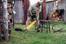 Mature Man Working With Grinder Saw Outdoors.