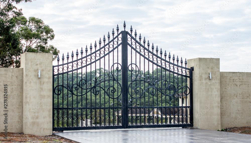 Fototapeta Black metal wrought iron driveway property entrance gates set in concrete brick fence, lights, garden trees in background