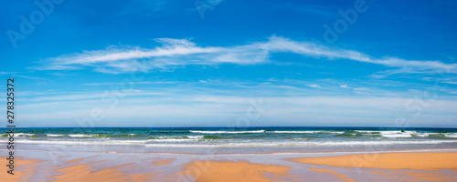 Fotografija  schöner Strand am Atlantik, mit Wellen und blauem Himmel mit feinen Wolken