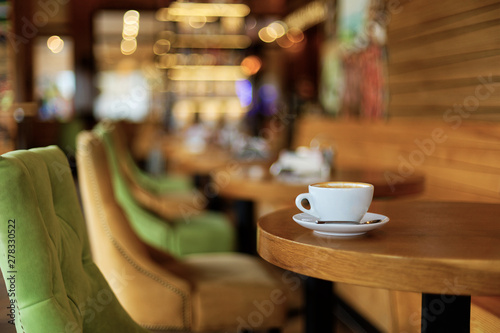 Cup of coffee cappuccino on a wooden table in a cafe. Shallow focus and lights on blurred background. Copyspace.