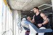 Side view portrait of young adult man in sportswear running on treadmill at gym. Handsome masculinity male training on treadmill and looking to window. Indoor, healthy fitness concept
