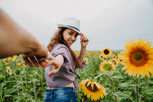 A Young Woman Leads A Man By The Hand In A Field Of Sunflowers, Looks Into The Frame And Smiles.