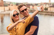 Portrait of the joyful young couple who is standing in the embrace against the background of the city and river and doing selfie photo