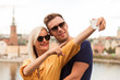Portrait of the happy young couple who is standing in the embrace against the background of the city and river and doing selfie photo