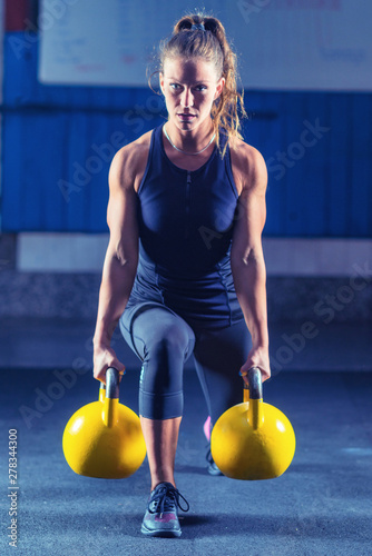 Fototapeta Woman athlete exercising with kettlebell