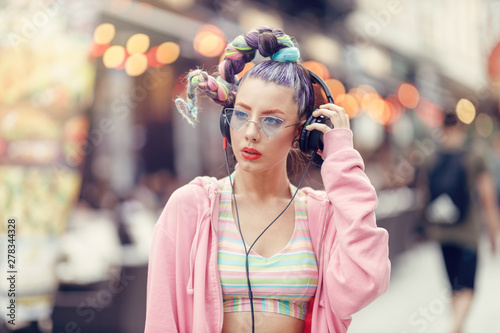 Fotografia Young girl with crazy avant-garde style listening music in headphones, Urban street style
