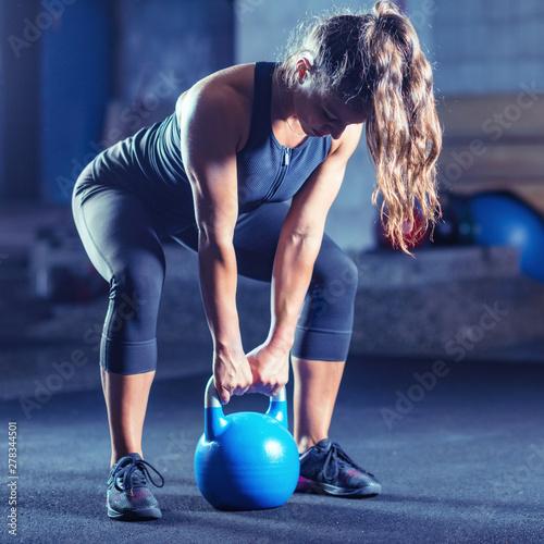 Obraz na plátně  Woman athlete exercising with kettlebell