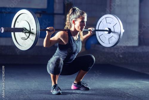 Obraz na plátně  Woman weightlifting on training