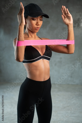 Fotografia Healthy beautiful woman working out with resistance band at the gym