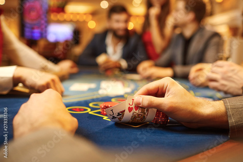 People play poker at the table in the casino. Canvas-taulu