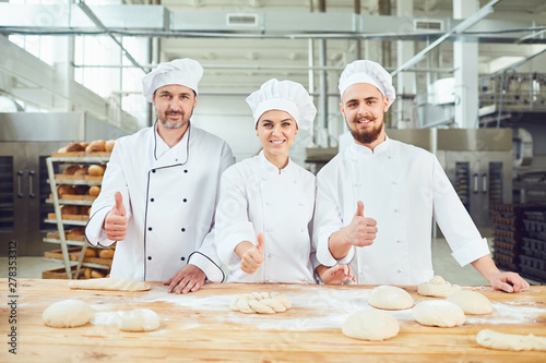 Stampa su Tela Bakers raised their thumbs up in bakery.