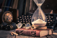 Aged Journal And Hourglass With Binocular, Compass And Books
