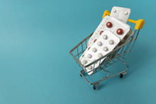 Shopping For Medicines, Healthcare Costs And Prescription Medication Concept With Shopping Cart Or Trolley Filled With Pills Isolated On Blue Background With Copy Space