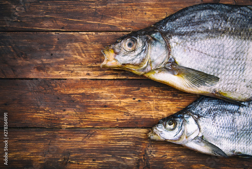 Poster Peche Two dried salted fish bream on a wooden table, vintage style, top view, text space