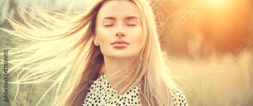 Obraz Portrait of beauty girl with fluttering white hair enjoying nature outdoors. Flying blonde hair on the wind. Beautiful young woman face closeup - fototapety do salonu