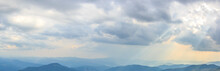 The Sun's Rays Penetrating Through The Clouds On The Surface Of The Mountains, Panoramic View.