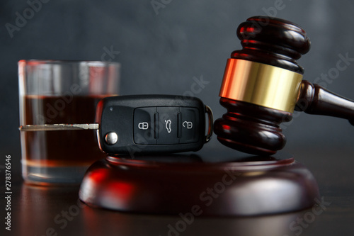 Bar The concept of a DUI. Law hammer, alcohol and car keys on wooden table, dark background