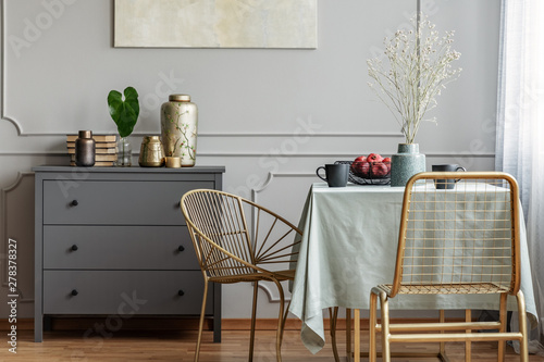 Fotografía  Dining room interior with long table, stylish golden chairs and grey wooden comm
