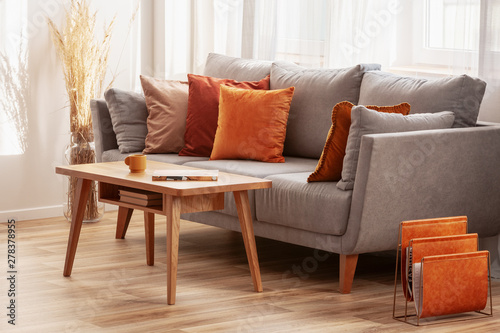 Vászonkép Living room with wooden coffee table and grey couch with ginger, orange and red